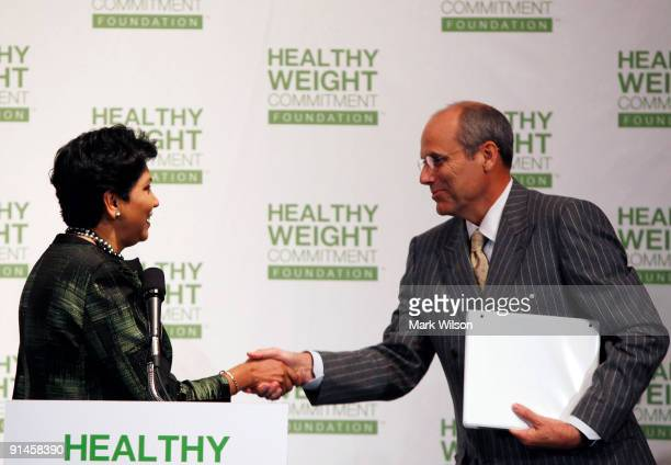 Dan Sanders CEO of United Supermarkets shakes hands with Indra Nooyi chairman and CEO of Pepsi Co speaks during a news conference at the National...