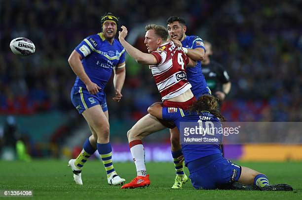 Dan Sarginson of Wigan offloads as Ashton Sims and Declan Patton of Warrington challenge during the First Utility Super League Final between...