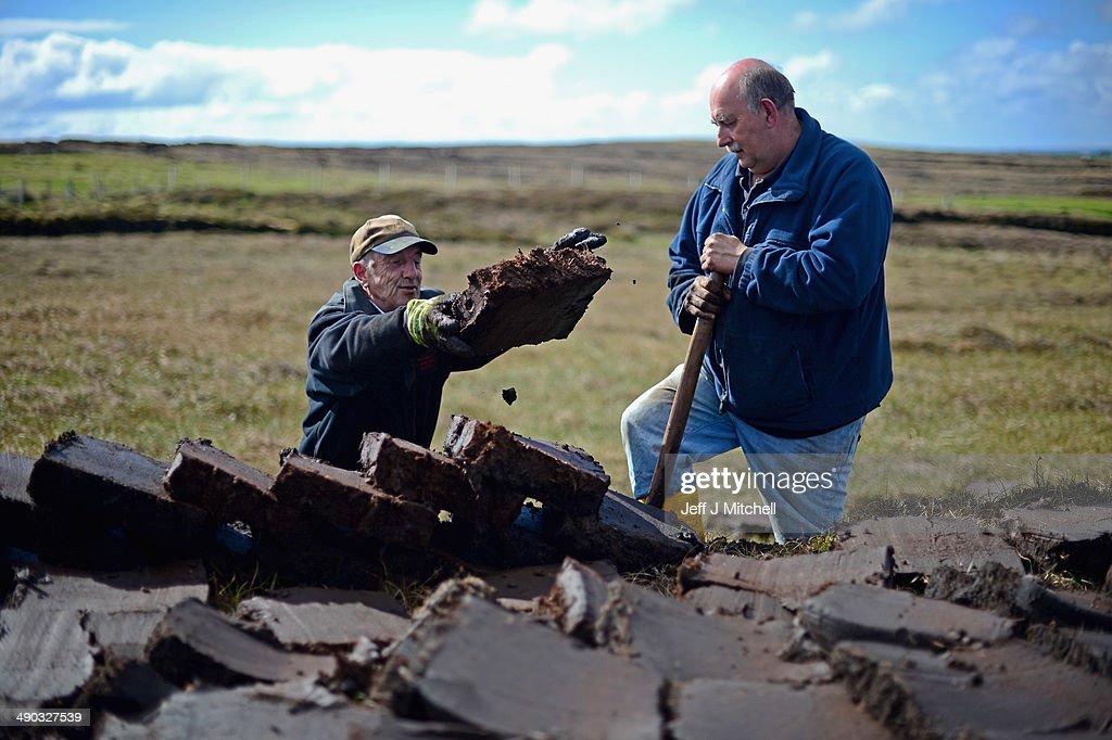 Dan Smith and Alastair Maclean extract peat from a moor near the village of Cross on May 13, 2014 in Lewis, Scotland. The tradition of peat cutting has seen a revival over recent years in the Outer Hebrides as residents conscious of rising fuel cost are using it to run their central heating and stove fires. A referendum on whether Scotland should be an independent country will take place on September 18, 2014.