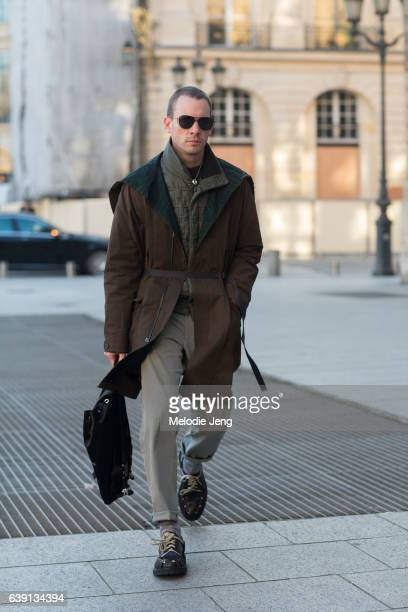 Dan Thawley wears a brown belted jacket over a green padded top and carries a black Alyx backpack outside the Balenciaga show at Place Vendome on...