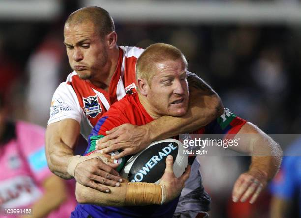Dan Tolar of the Knights is tackled by Matt Cooper of the Dragons during the round 25 NRL match between the Newcastle Knights and the St George...