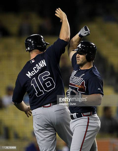Dan Uggla and Brian McCann of the Atlanta Braves celebrate after Uggla's three run home run iin the ninth inning against the Los Angeles Dodgers on...