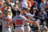 Dan Uggla and Chipper Jones of the Atlanta Braves celebrate after they scored in the 10th inning against the San Francisco Giants at ATT Park on...