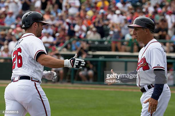 Dan Uggla highfives third base coach third base coach Doug Dascenzo of the Atlanta Braves after hitting a home run during the game against the...