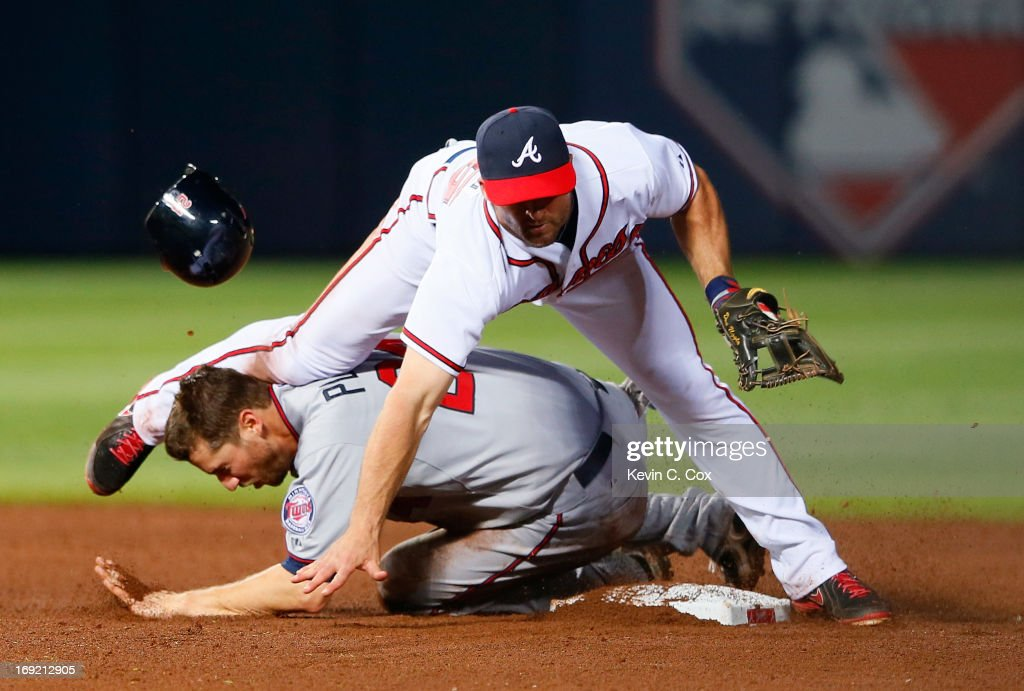 <a gi-track='captionPersonalityLinkClicked' href=/galleries/search?phrase=Dan+Uggla&family=editorial&specificpeople=542208 ng-click='$event.stopPropagation()'>Dan Uggla</a> #26 of the Atlanta Braves attempts a double play ball as he collides into a sliding <a gi-track='captionPersonalityLinkClicked' href=/galleries/search?phrase=Trevor+Plouffe&family=editorial&specificpeople=5722348 ng-click='$event.stopPropagation()'>Trevor Plouffe</a> #24 of the Minnesota Twins in the 10th inning at Turner Field on May 21, 2013 in Atlanta, Georgia.