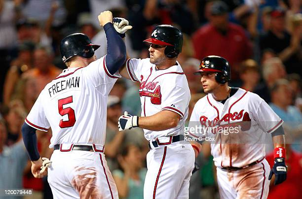 Dan Uggla of the Atlanta Braves celebrates his threerun homer in the seventh inning against the Florida Marlins with Freddie Freeman and Martin Prado...