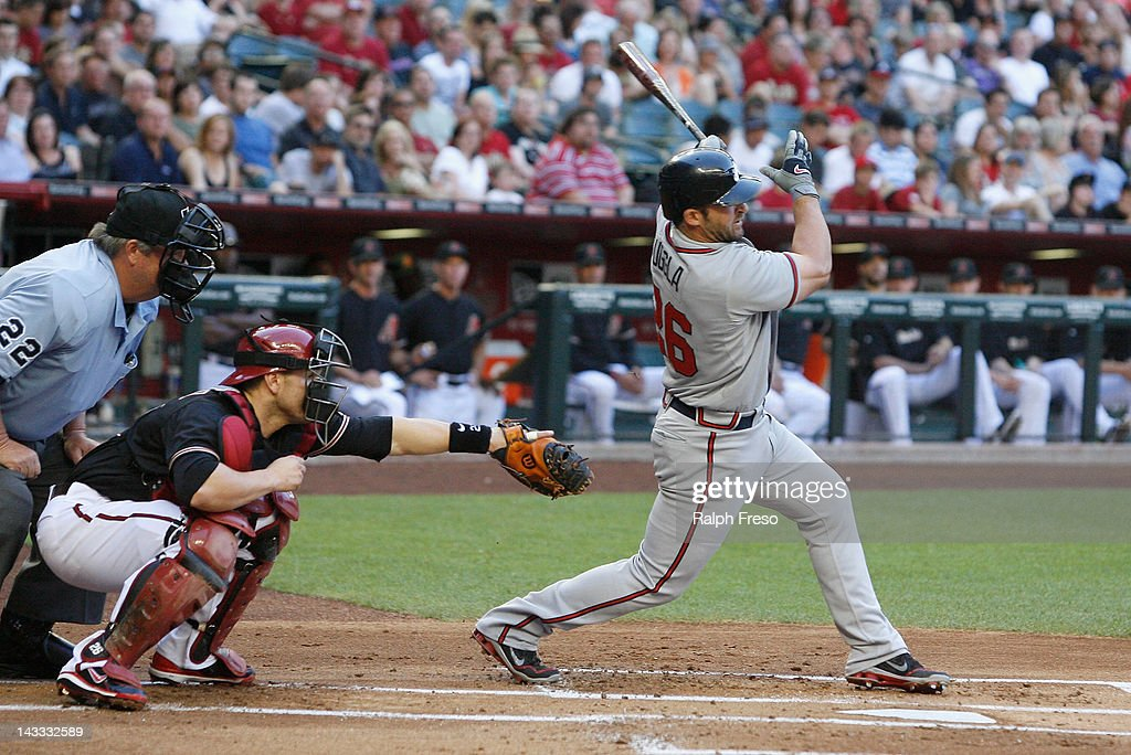 Dan Uggla of the Atlanta Braves fouls off a pitch in front of Miguel Montero of the Arizona Diamondbacks and home plate umpire Joe West during the...