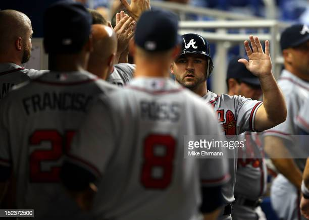 Dan Uggla of the Atlanta Braves is congratulated after scoring during a game against the Miami Marlins at Marlins Park on September 19 2012 in Miami...