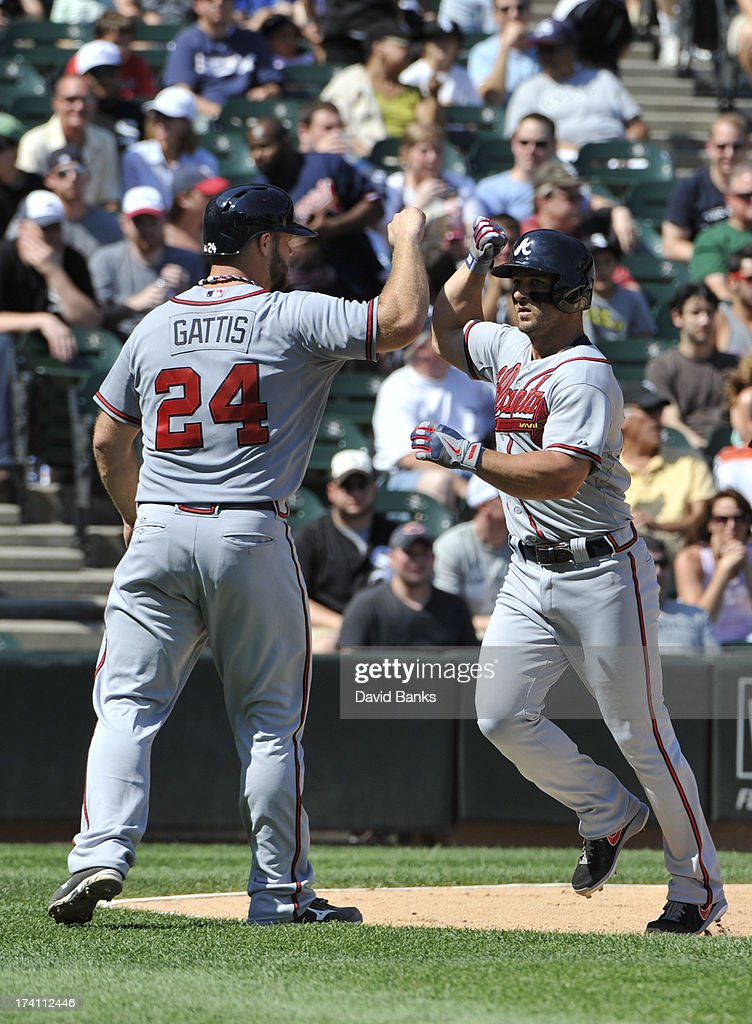Dan Uggla #26 of the Atlanta Braves is greeted by Evan Gattis #24 after hitting a two-run homer during the second inning against the Chicago White Sox on July 20, 2013 at U.S. Cellular Field in Chicago, Illinois.