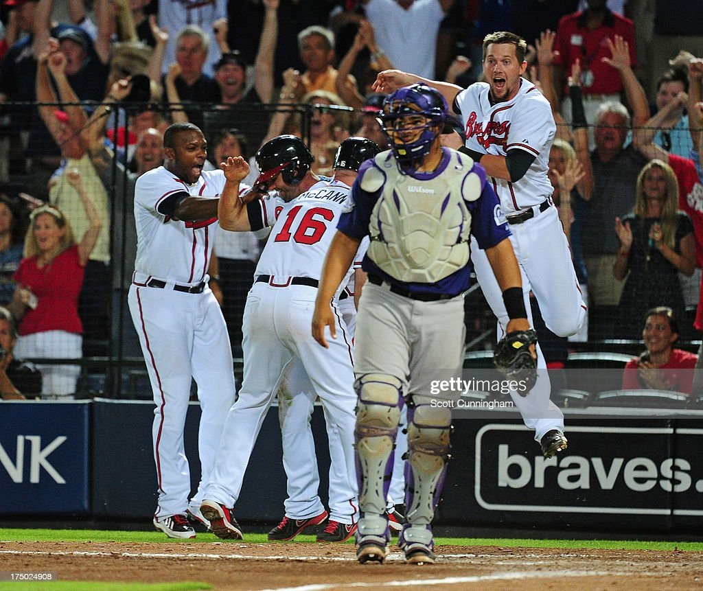 <a gi-track='captionPersonalityLinkClicked' href=/galleries/search?phrase=Dan+Uggla&family=editorial&specificpeople=542208 ng-click='$event.stopPropagation()'>Dan Uggla</a> #26 of the Atlanta Braves is mobbed by teammates after scoring the game-winning run in the 10th inning against the Colorado Rockies at Turner Field on July 29, 2013 in Atlanta, Georgia.