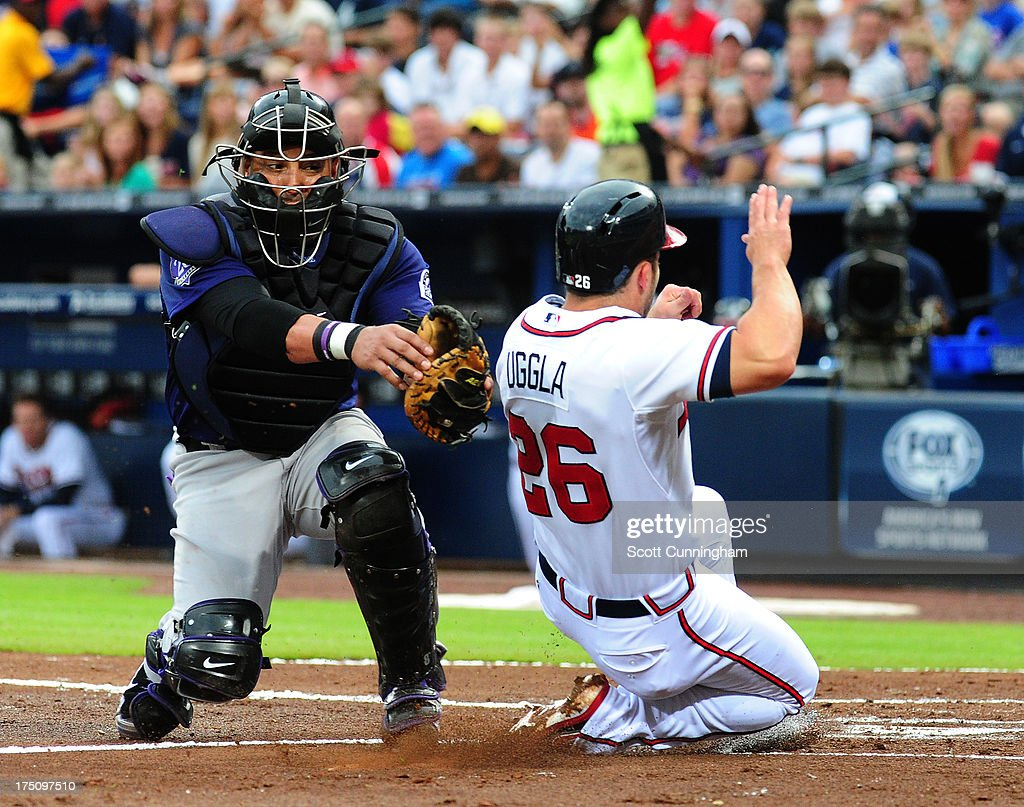 <a gi-track='captionPersonalityLinkClicked' href=/galleries/search?phrase=Dan+Uggla&family=editorial&specificpeople=542208 ng-click='$event.stopPropagation()'>Dan Uggla</a> #26 of the Atlanta Braves is tagged out at home by <a gi-track='captionPersonalityLinkClicked' href=/galleries/search?phrase=Yorvit+Torrealba&family=editorial&specificpeople=212721 ng-click='$event.stopPropagation()'>Yorvit Torrealba</a> #8 of the Colorado Rockies at Turner Field on July 31, 2013 in Atlanta, Georgia.