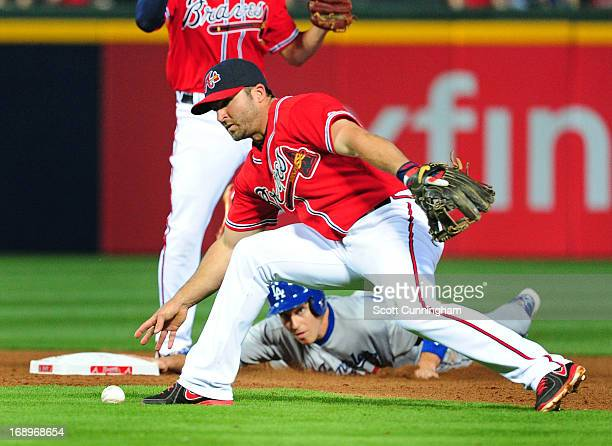 Dan Uggla of the Atlanta Braves is unable to field a ground ball as A J Ellis of the Los Angeles Dodgers advances to second base at Turner Field on...