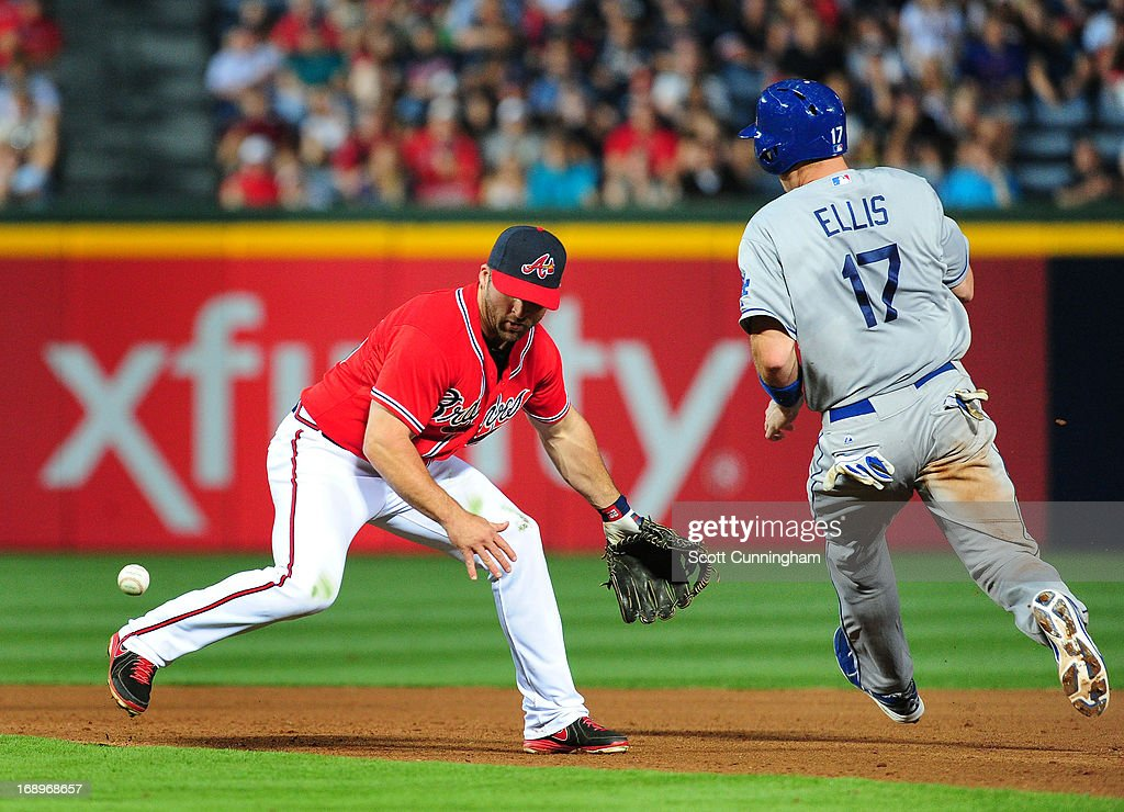 <a gi-track='captionPersonalityLinkClicked' href=/galleries/search?phrase=Dan+Uggla&family=editorial&specificpeople=542208 ng-click='$event.stopPropagation()'>Dan Uggla</a> #26 of the Atlanta Braves is unable to field a ground ball as <a gi-track='captionPersonalityLinkClicked' href=/galleries/search?phrase=A.+J.+Ellis&family=editorial&specificpeople=6925614 ng-click='$event.stopPropagation()'>A. J. Ellis</a> #17 of the Los Angeles Dodgers advances to second base at Turner Field on May 17, 2013 in Atlanta, Georgia.