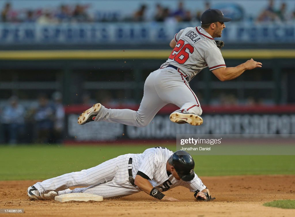 <a gi-track='captionPersonalityLinkClicked' href=/galleries/search?phrase=Dan+Uggla&family=editorial&specificpeople=542208 ng-click='$event.stopPropagation()'>Dan Uggla</a> #26 of the Atlanta Braves leaps over <a gi-track='captionPersonalityLinkClicked' href=/galleries/search?phrase=Gordon+Beckham&family=editorial&specificpeople=5411079 ng-click='$event.stopPropagation()'>Gordon Beckham</a> #15 of the Chicago White Sox while trying to turn a double play at U.S. Cellular Field on July 19, 2013 in Chicago, Illinois.