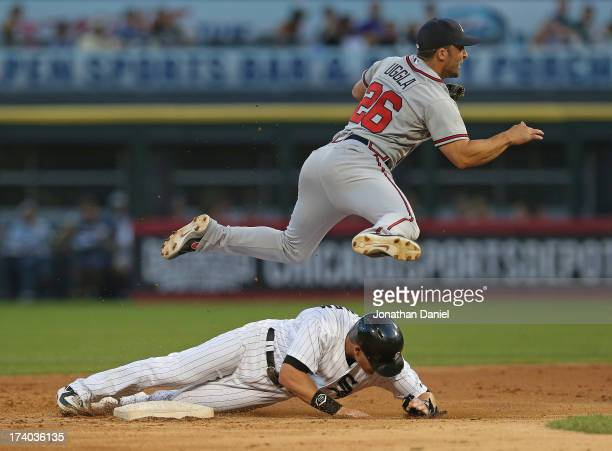 Dan Uggla of the Atlanta Braves leaps over Gordon Beckham of the Chicago White Sox while trying to turn a double play at US Cellular Field on July 19...