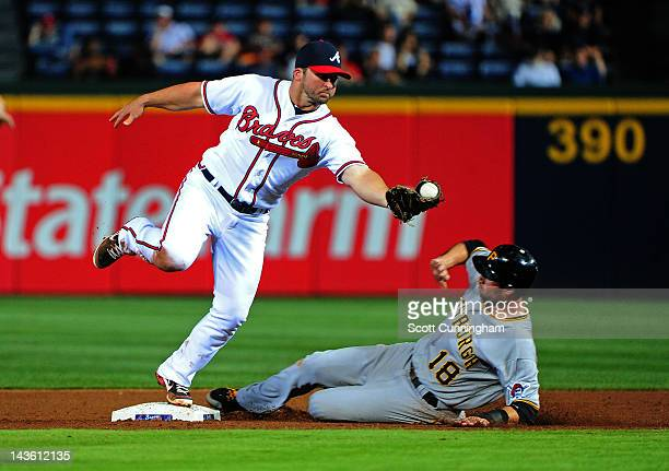 Dan Uggla of the Atlanta Braves makes a catch to force out Neil Walker of the Pittsburgh Pirates at Turner Field on April 30 2012 in Atlanta Georgia
