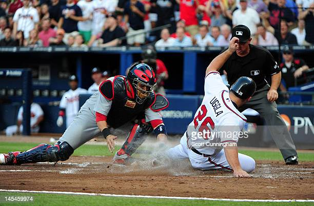 Dan Uggla of the Atlanta Braves slides in to score against Yadier Molina of the St Louis Cardinals at Turner Field on May 30 2012 in Atlanta Georgia