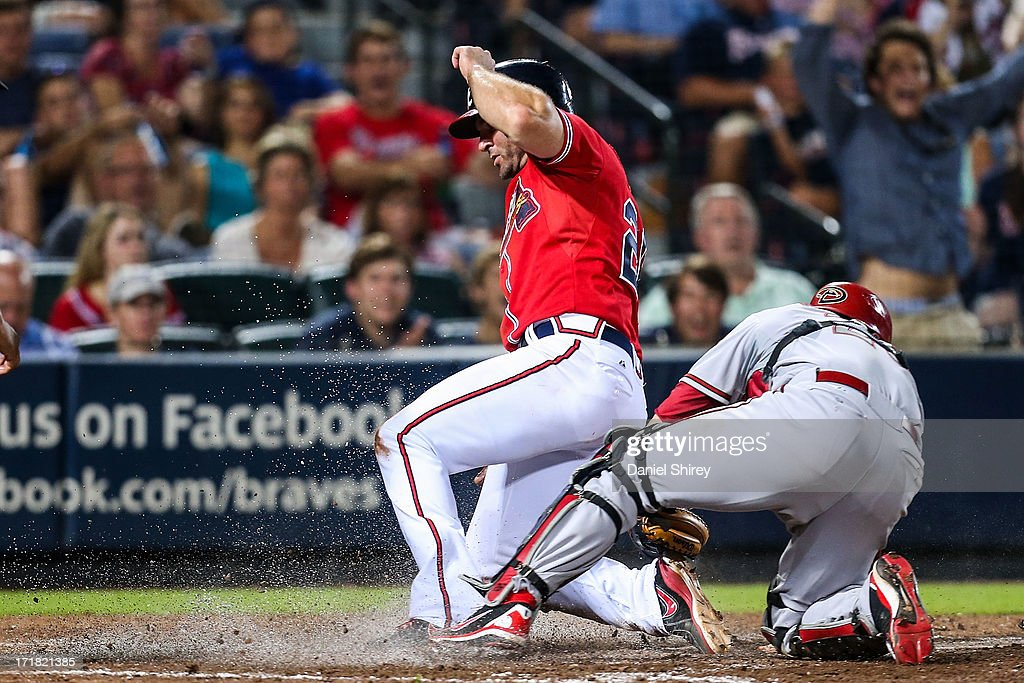 <a gi-track='captionPersonalityLinkClicked' href=/galleries/search?phrase=Dan+Uggla&family=editorial&specificpeople=542208 ng-click='$event.stopPropagation()'>Dan Uggla</a> #26 of the Atlanta Braves slides into home on a squeeze play before the tag by <a gi-track='captionPersonalityLinkClicked' href=/galleries/search?phrase=Miguel+Montero&family=editorial&specificpeople=836495 ng-click='$event.stopPropagation()'>Miguel Montero</a> #26 of the Arizona Diamondbacks in the eighth inning at Turner Field on June 28, 2013 in Atlanta, Georgia.