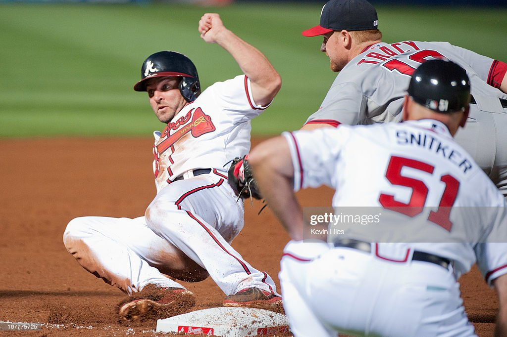 <a gi-track='captionPersonalityLinkClicked' href=/galleries/search?phrase=Dan+Uggla&family=editorial&specificpeople=542208 ng-click='$event.stopPropagation()'>Dan Uggla</a> #26 of the Atlanta Braves slides into third base as <a gi-track='captionPersonalityLinkClicked' href=/galleries/search?phrase=Chad+Tracy&family=editorial&specificpeople=213807 ng-click='$event.stopPropagation()'>Chad Tracy</a> #18 of the Washington Nationals makes the tag the fourth inning at Turner Field on April 29, 2013 in Atlanta, Georgia. Uggla was called out on the play. The Braves defeated the Nationals 3-2.