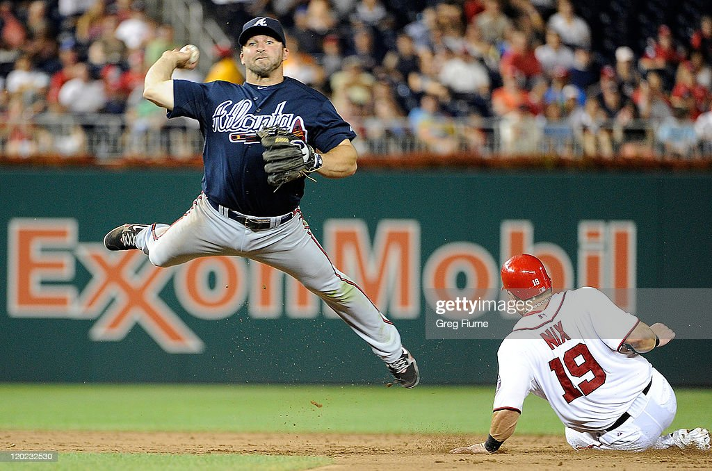 <a gi-track='captionPersonalityLinkClicked' href=/galleries/search?phrase=Dan+Uggla&family=editorial&specificpeople=542208 ng-click='$event.stopPropagation()'>Dan Uggla</a> #26 of the Atlanta Braves throws the ball into the stands for an error after forcing out <a gi-track='captionPersonalityLinkClicked' href=/galleries/search?phrase=Laynce+Nix&family=editorial&specificpeople=214636 ng-click='$event.stopPropagation()'>Laynce Nix</a> #19 of the Washington Nationals at Nationals Park on August 1, 2011 in Washington, DC.