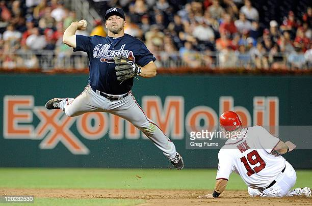 Dan Uggla of the Atlanta Braves throws the ball into the stands for an error after forcing out Laynce Nix of the Washington Nationals at Nationals...