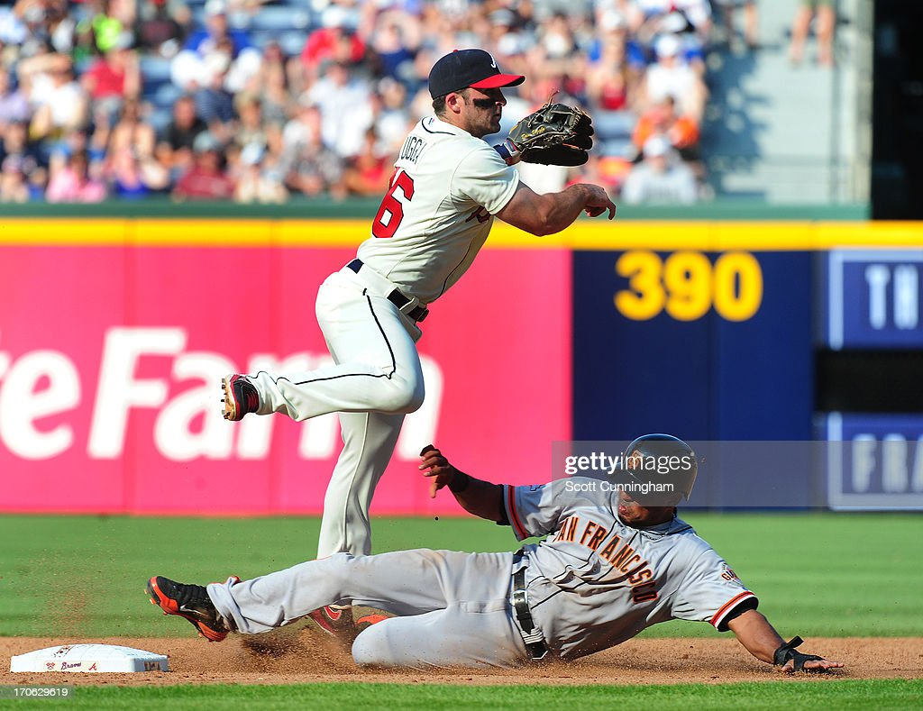 <a gi-track='captionPersonalityLinkClicked' href=/galleries/search?phrase=Dan+Uggla&family=editorial&specificpeople=542208 ng-click='$event.stopPropagation()'>Dan Uggla</a> #26 of the Atlanta Braves turns a double play against <a gi-track='captionPersonalityLinkClicked' href=/galleries/search?phrase=Tony+Abreu&family=editorial&specificpeople=840737 ng-click='$event.stopPropagation()'>Tony Abreu</a> #10 of the San Francisco Giants at Turner Field on June 15, 2013 in Atlanta, Georgia.