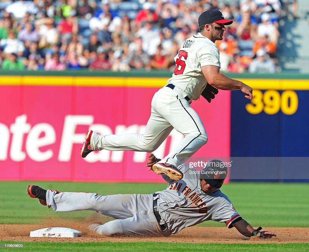 Dan Uggla #26 of the Atlanta Braves turns a double play against Tony Abreu #10 of the San Francisco Giants at Turner Field on June 15, 2013 in Atlanta, Georgia.