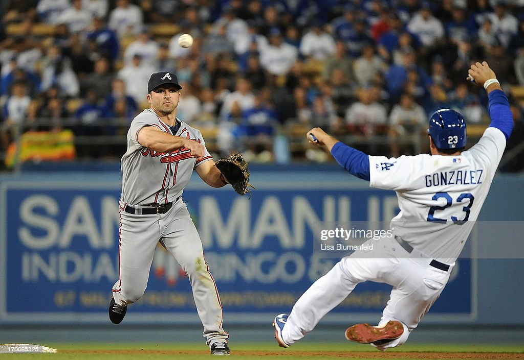 <a gi-track='captionPersonalityLinkClicked' href=/galleries/search?phrase=Dan+Uggla&family=editorial&specificpeople=542208 ng-click='$event.stopPropagation()'>Dan Uggla</a> #26 of the Atlanta Braves turns a double play in the seventh inning against Adrian Gonzalez #23 of the Los Angeles Dodgers at Dodger Stadium on June 6, 2013 in Los Angeles, California.
