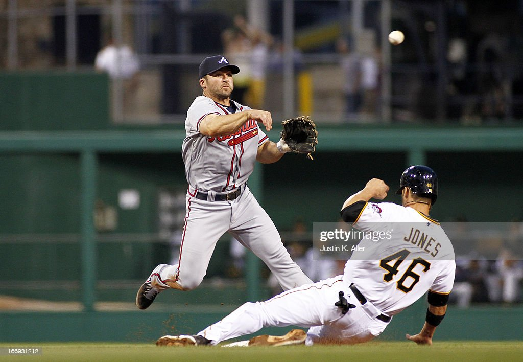 Dan Uggla #26 of the Atlanta Braves turns a double play in the third inning over a sliding Garrett Jones #46 of the Pittsburgh Pirates during the game on April 18, 2013 at PNC Park in Pittsburgh, Pennsylvania.