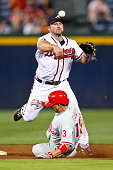 Dan Uggla of the Atlanta Braves turns a double play over Freddy Galvis of the Philadelphia Phillies in the ninth inning on May 1 2012 at Turner Field...