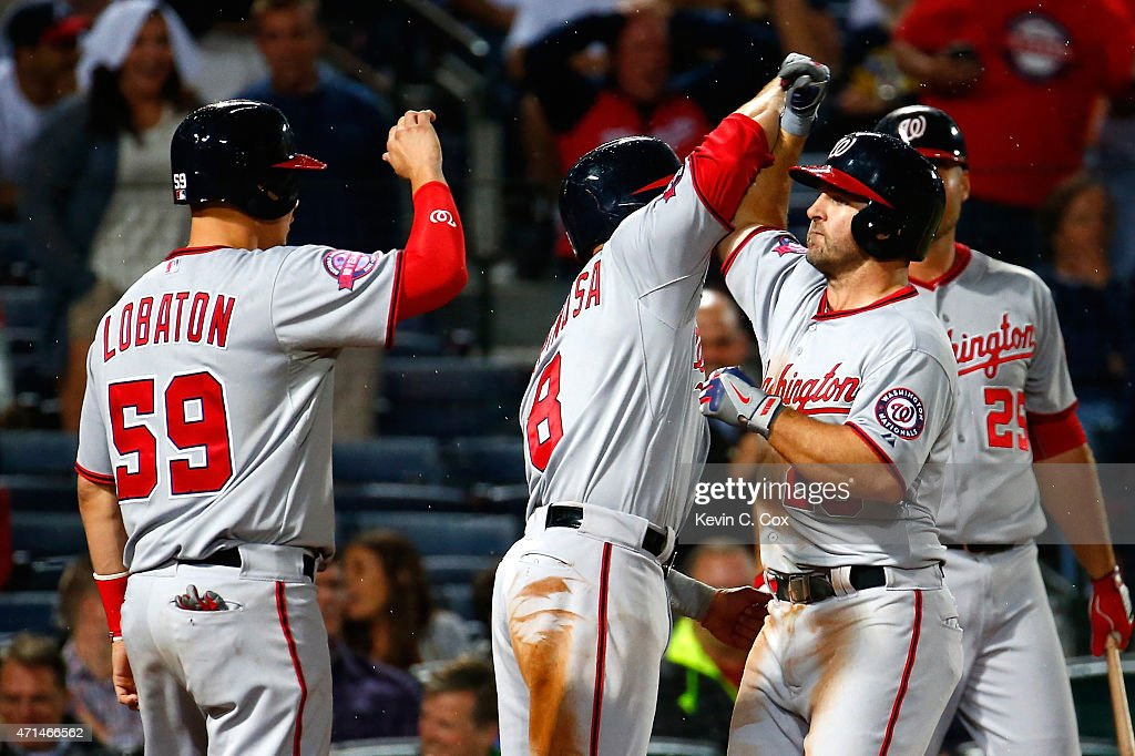<a gi-track='captionPersonalityLinkClicked' href=/galleries/search?phrase=Dan+Uggla&family=editorial&specificpeople=542208 ng-click='$event.stopPropagation()'>Dan Uggla</a> #26 of the Washington Nationals celebrates after hitting a three-run homer in the ninth inning to score Jose Lobaton #59 and <a gi-track='captionPersonalityLinkClicked' href=/galleries/search?phrase=Danny+Espinosa&family=editorial&specificpeople=4410764 ng-click='$event.stopPropagation()'>Danny Espinosa</a> #8 against the Atlanta Braves at Turner Field on April 28, 2015 in Atlanta, Georgia.