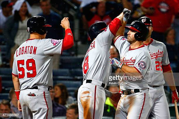 Dan Uggla of the Washington Nationals celebrates after hitting a threerun homer in the ninth inning to score Jose Lobaton and Danny Espinosa against...