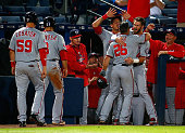 Dan Uggla of the Washington Nationals celebrates with Bryce Harper after hitting a threerun homer in the ninth inning to score Jose Lobaton and Danny...
