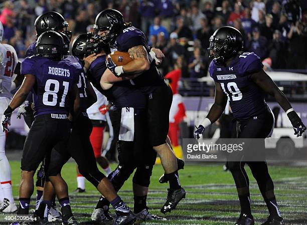 Dan Vitale fullback of the Northwestern Wildcats is greeted by his teammates after a touchdown against the Ball State Cardinals during the first half...
