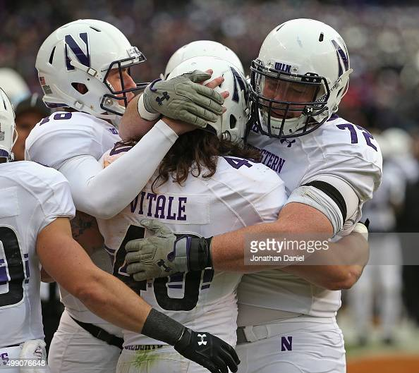 Dan Vitale of the Northwestern Wildcats is hugged by teammates Clayton Thorson and Blake Hance after catching touchdown pass against the Illinois...