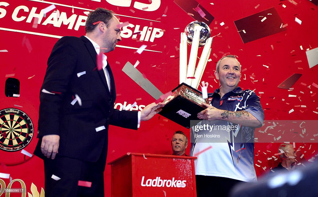 Dan Waddell, the son of the late Sid Waddell, presents Phil Taylor of England with the trophy after he won the final of the 2013 Ladbrokes.com World Darts Championship at the Alexandra Palace on January 1, 2013 in London, England.
