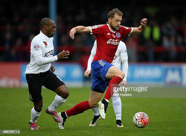 Dan Walker of Aldershot advances under pressure from Kyel Reid of Bradford during The Emirates FA Cup First Round match between Aldershot Town and...