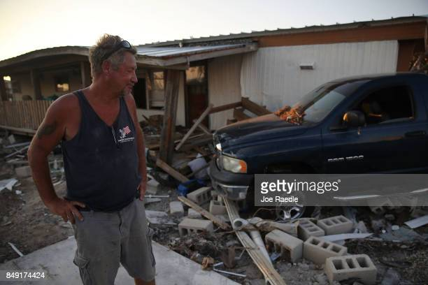 Dan Weeks stands near where his destroyed mobile home once stood as his pickup truck sits against his neighbors home after hurricane Irma passed...