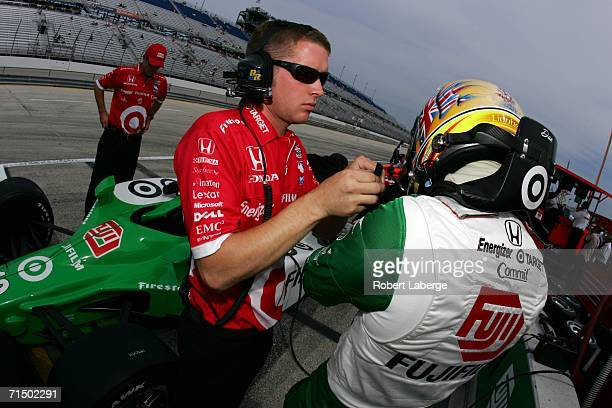 Dan Wheldon driver of the Chip Ganassi Racing Fujifilm Dallara Honda gets ready for practice as a team member helps him put his helmet on before...