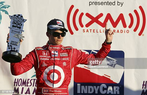 Dan Wheldon driver of the Target Ganassi Racing Dallara Honda holds up the winners trophy during the IRL Indycar Series Toyota Indy 300 on March 26...
