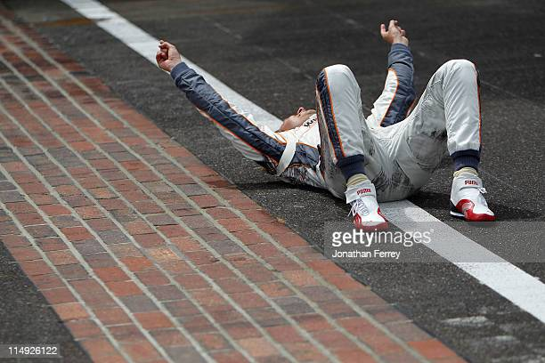 Dan Wheldon of England driver of the William RastCurb/Big Machine Dallara Honda celebrates at the start/finish line after winning the IZOD IndyCar...