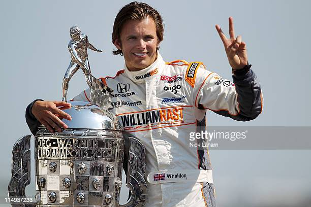 Dan Wheldon of England driver of the William RastCurb/Big Machine Dallara Honda poses with Borg Warner Trophy on the yard of bricks during the 95th...
