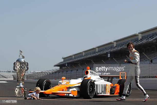 Dan Wheldon of England driver of the William RastCurb/Big Machine Dallara Honda leaves son Sebastian with the Borg Warner Trophy on the yard of...