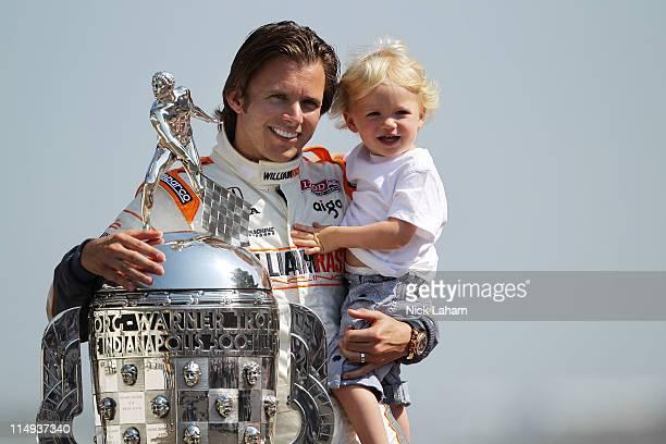 Dan Wheldon of England driver of the William RastCurb/Big Machine Dallara Honda poses with Borg Warner Trophy on the yard of bricks and son Sebastian...