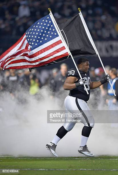 Dan Williams of the Oakland Raiders carring the American Flag runs onto the field during player introductions prior to playing the Denver Broncos in...