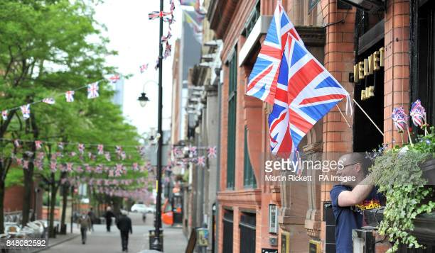 Dan Williams puts up a union flag at during preparations for a Jubilee street party on Canal Street in Manchester
