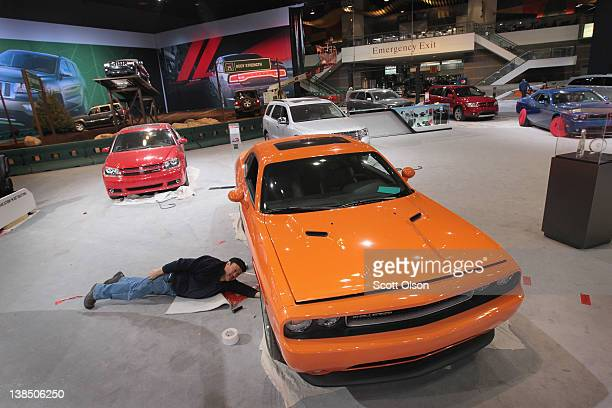 Dan Zapata prepares a Dodge Challenger for display at the Chicago Auto Show on February 7 2012 in Chicago Illinois The show which is the largest and...