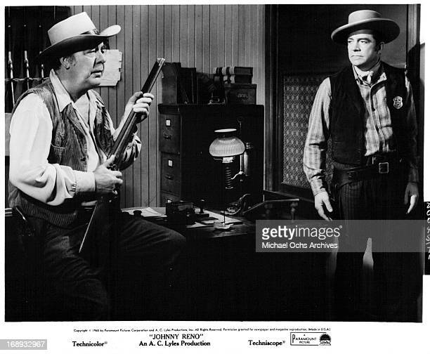 Dana Andrews stands looking at Lon Chaney Jrholding rifle in a scene from the film 'Johnny Reno' 1966