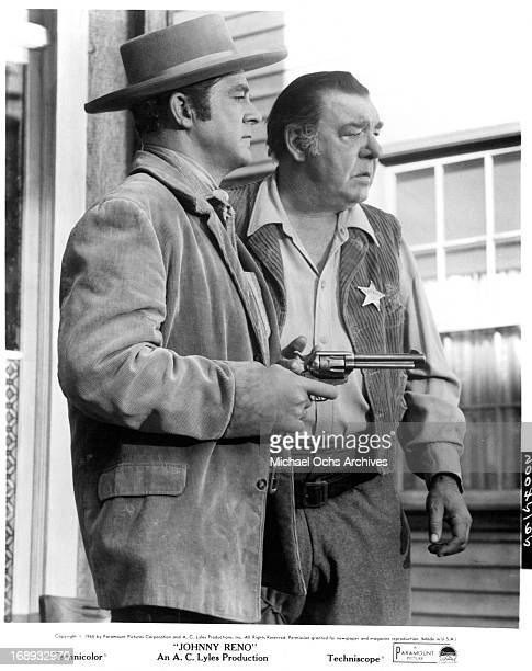 Dana Andrews with a pointed gun stands next to Lon Chaney Jr in a scene from the film 'Johnny Reno' 1966