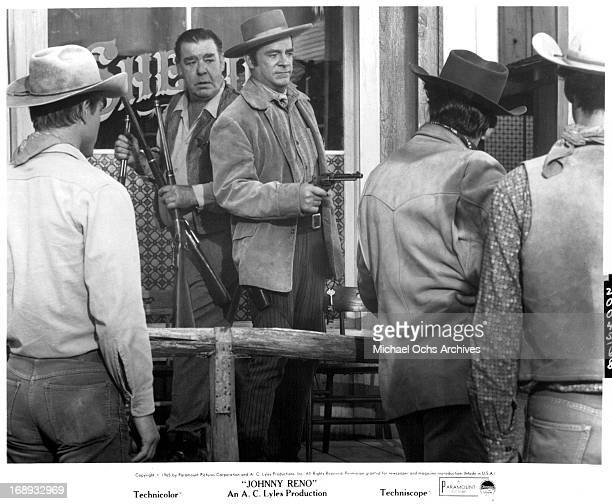 Dana Andrews with a pointed gun stands next to Lon Chaney Jrholding three rifles in a scene from the film 'Johnny Reno' 1966